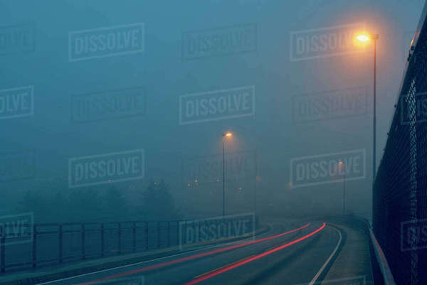 Diminishing perspective of light trails on misty road illuminated by street lights, Haugesund, Rogaland County, Norway Royalty-free stock photo