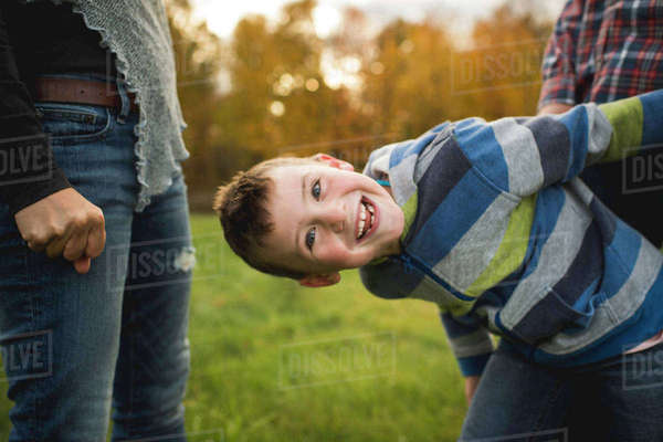 Boy with parents bending forwards looking at camera smiling Royalty-free stock photo