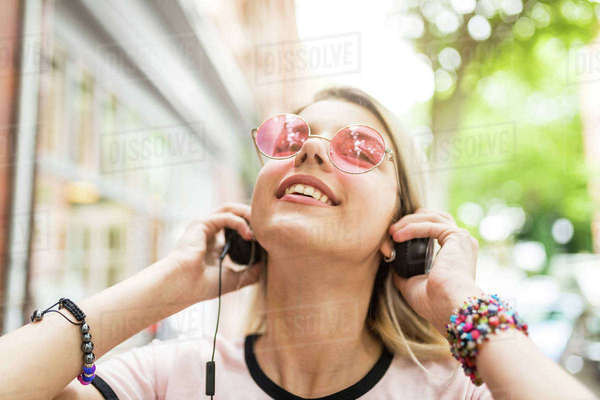 Teenage girl outdoors, wearing headphones, listening to music Royalty-free stock photo