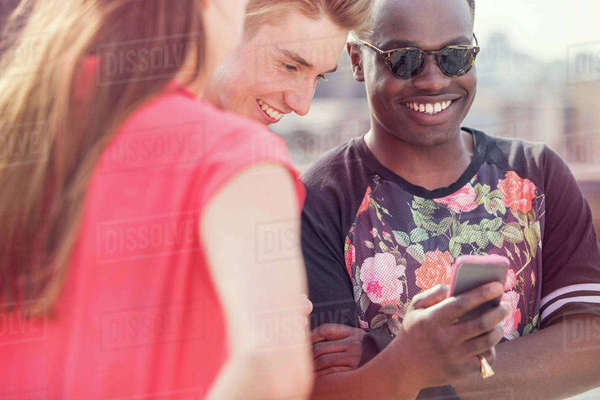 Three young adult friends looking at smartphone at roof party in London, UK Royalty-free stock photo