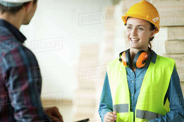 Two people standing in constructions site, wearing hard hats, having discussion Royalty-free stock photo