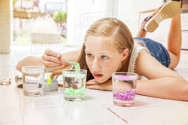 Girl lying on floor doing experiment with glasses of water Royalty-free stock photo