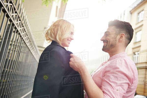 Man in street sharing suit jacket with woman Royalty-free stock photo