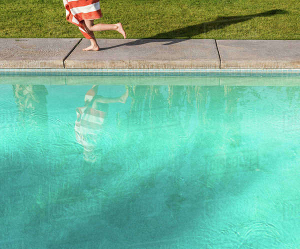 Waist down view of boy wrapped in towel running on poolside Royalty-free stock photo