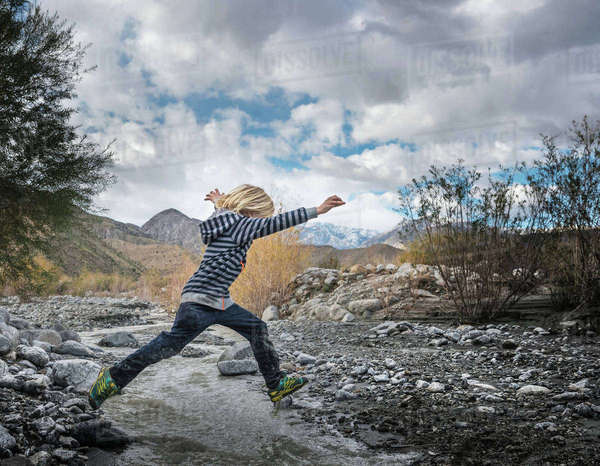 Boy leaping over rocks on riverbed Royalty-free stock photo