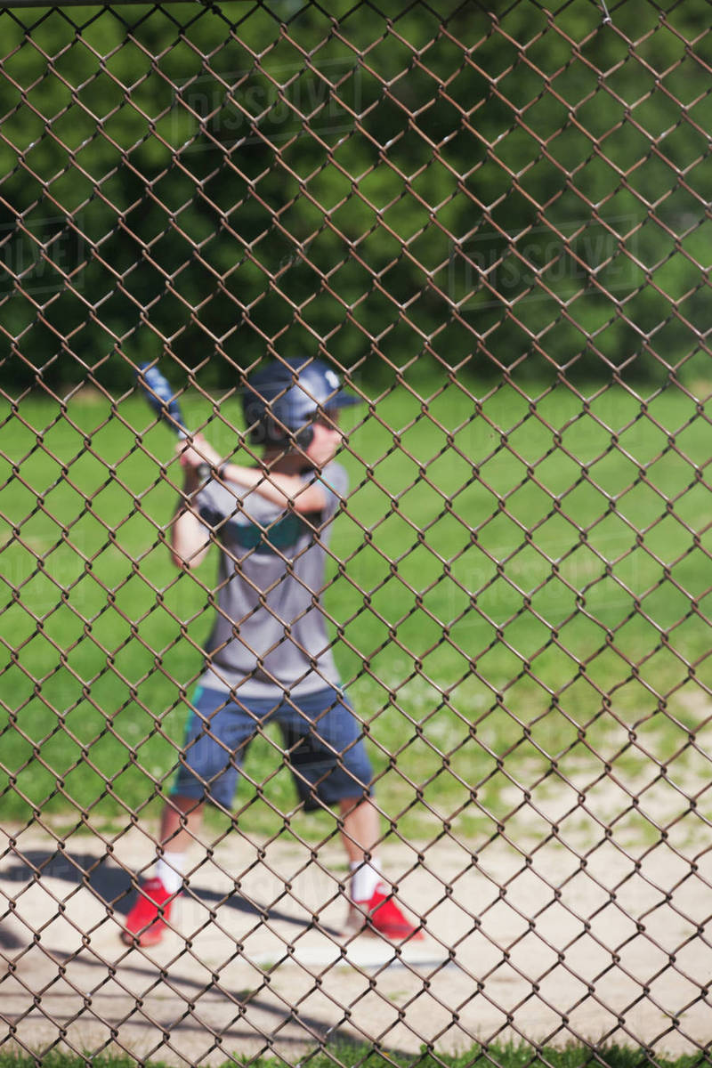 View through chicken wire fence of boy playing baseball - Stock ...
