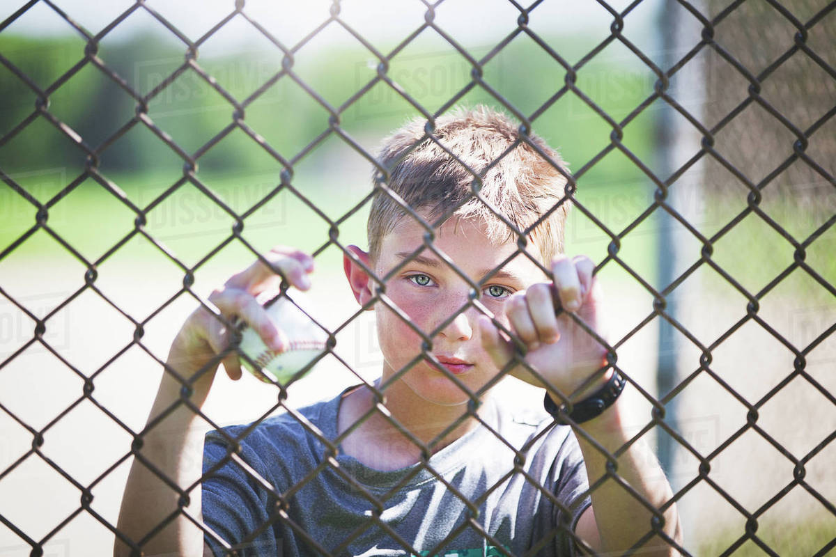 View through chicken wire fence of boy looking at camera - Stock ...