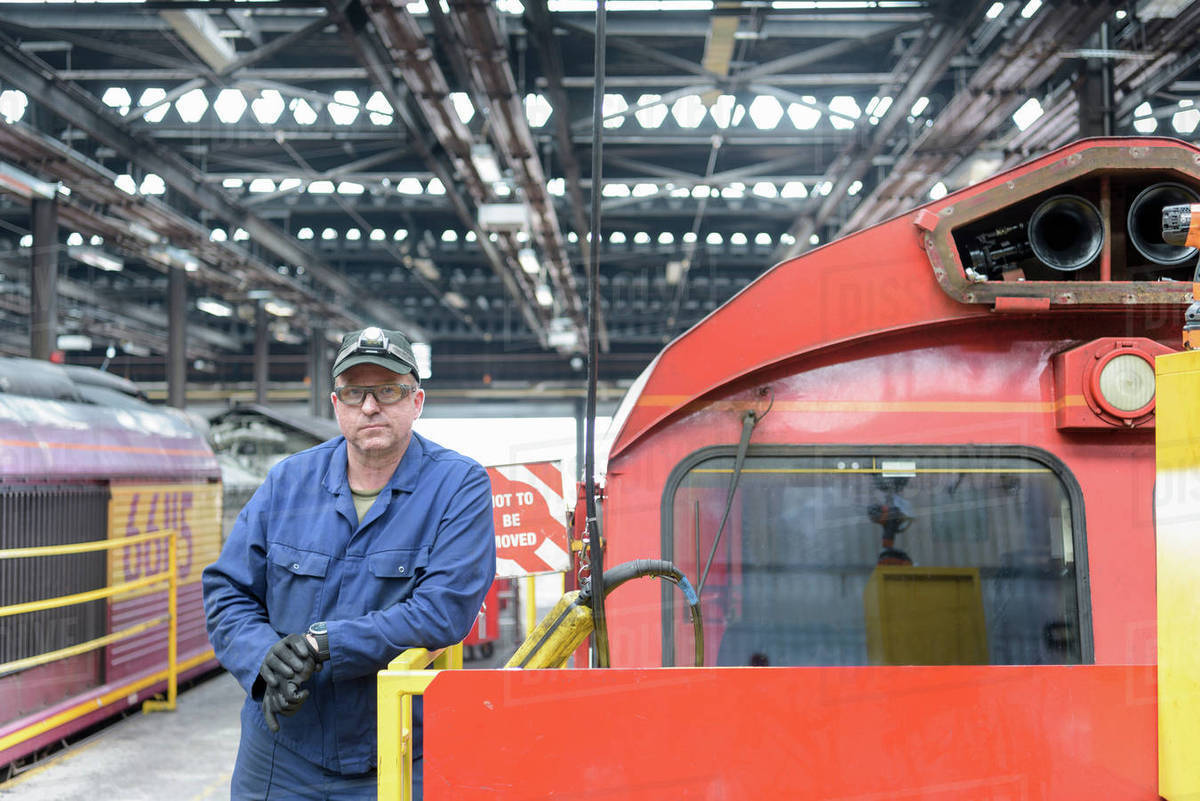 Portrait of locomotive engineer working in train works stock photo