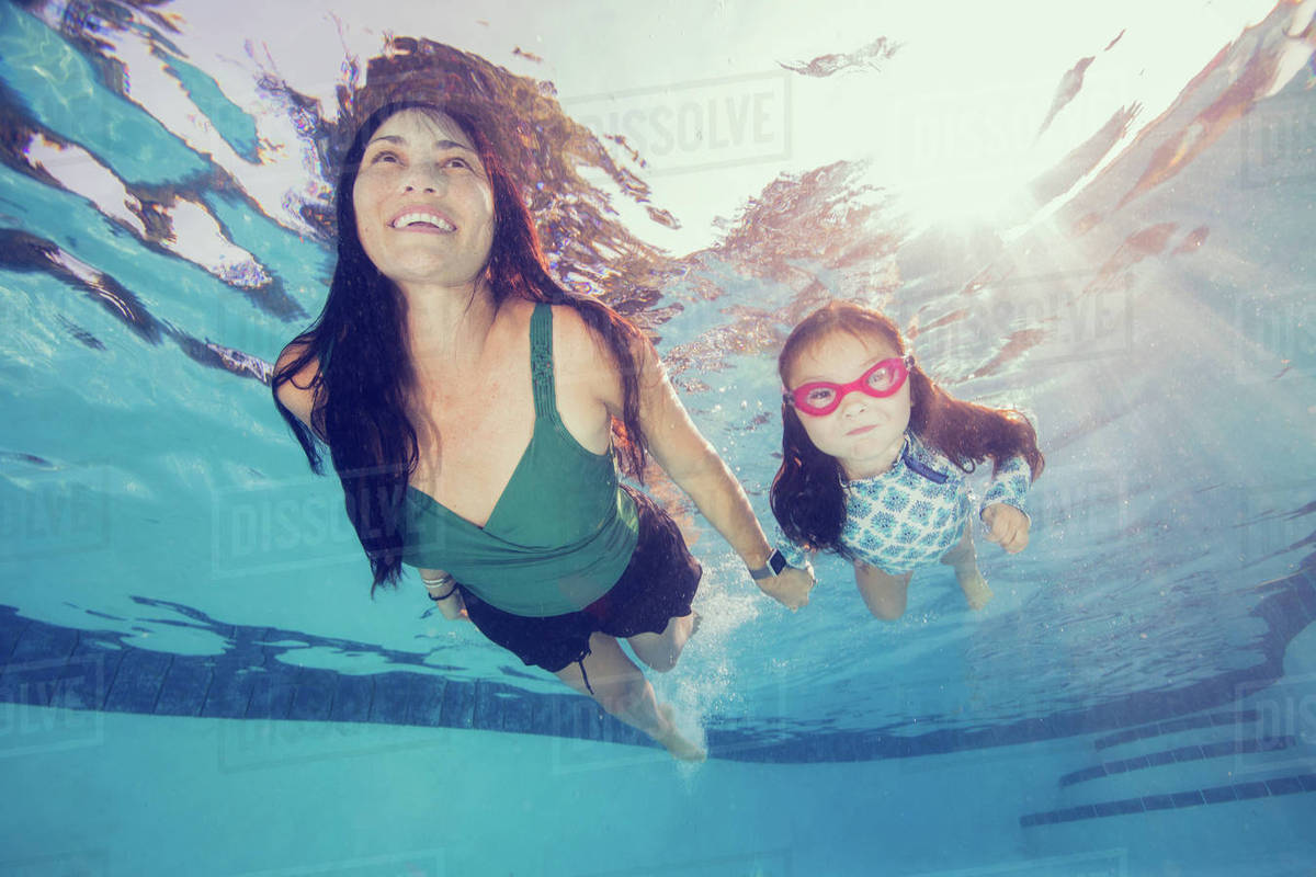 Underwater view of mature woman swimming holding daughter's hand