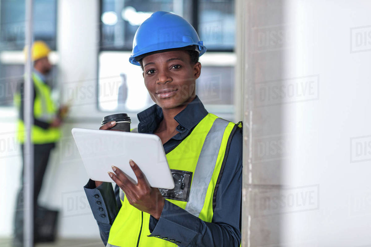woman with hard hat and hi viz jacket using digital tablet stock