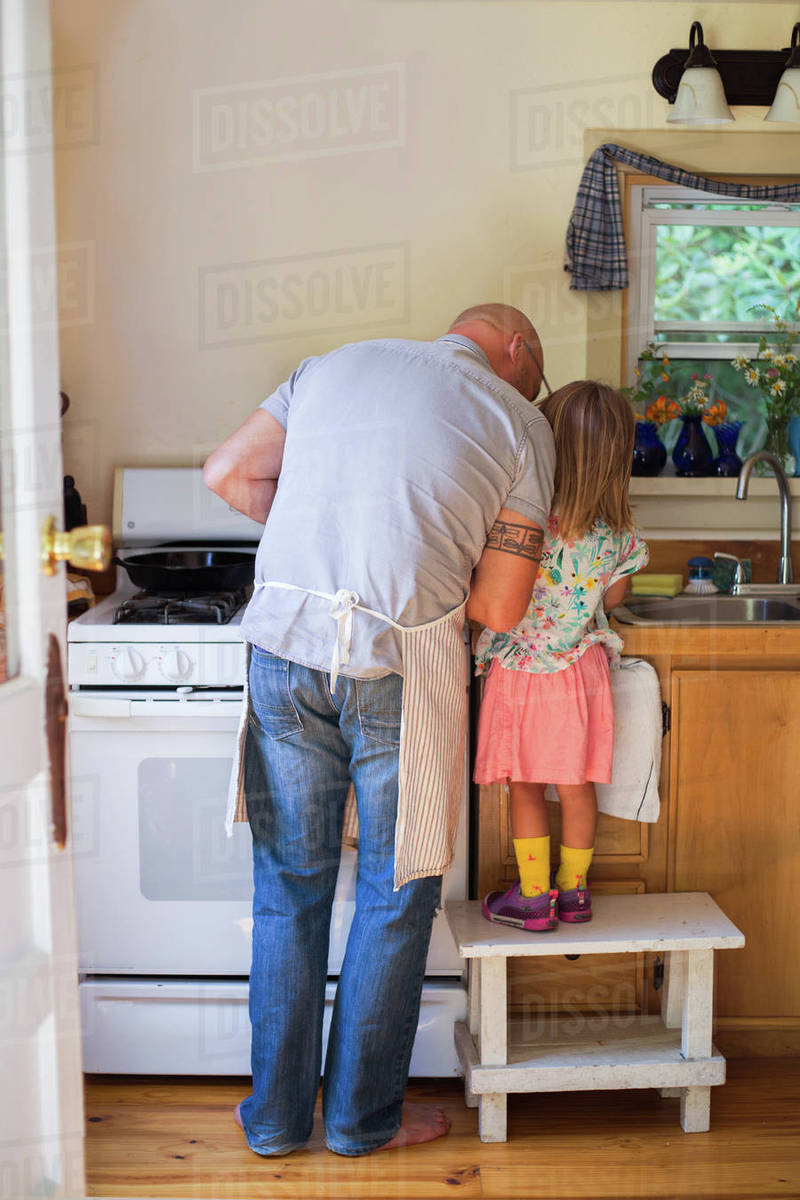 Phenomenal Rear View Of Girl On Stool Watching Father Preparing Food In Kitchen Stock Photo Creativecarmelina Interior Chair Design Creativecarmelinacom