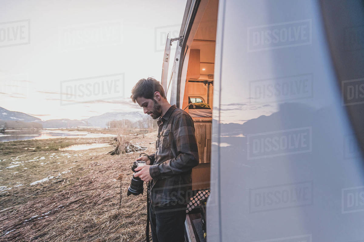 A man standing beside a van looking down at a camera in his hands, rocky landscape in the background. Royalty-free stock photo