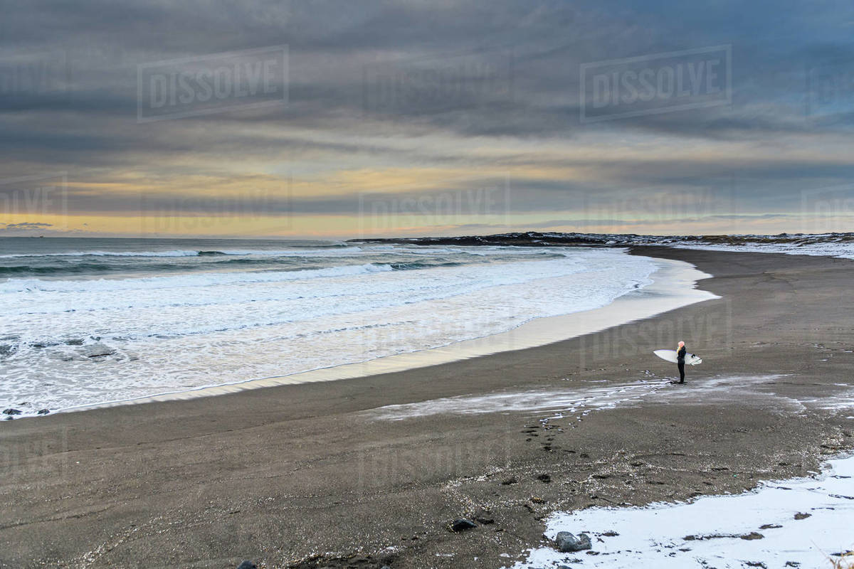 A woman holding a surfboard on a beach looking out to sea, in winter. Royalty-free stock photo