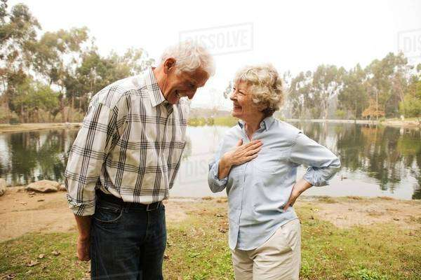 Husband and wife sharing joke by the lake Royalty-free stock photo
