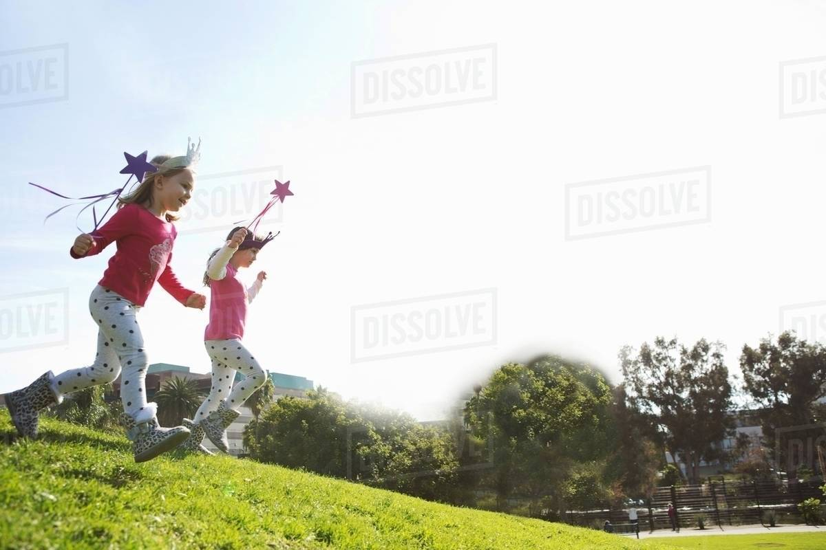 Two young sisters dressed up as fairies running down hill Royalty-free stock photo