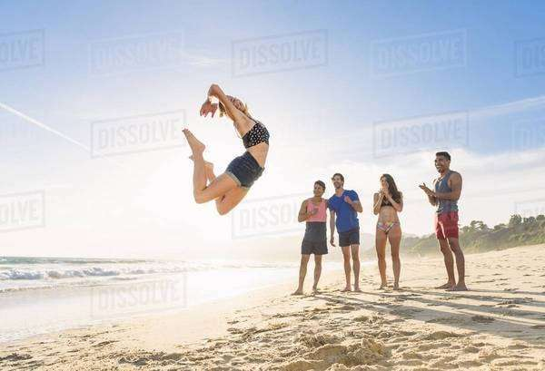 Group of friends on beach watching friend leap in air Royalty-free stock photo