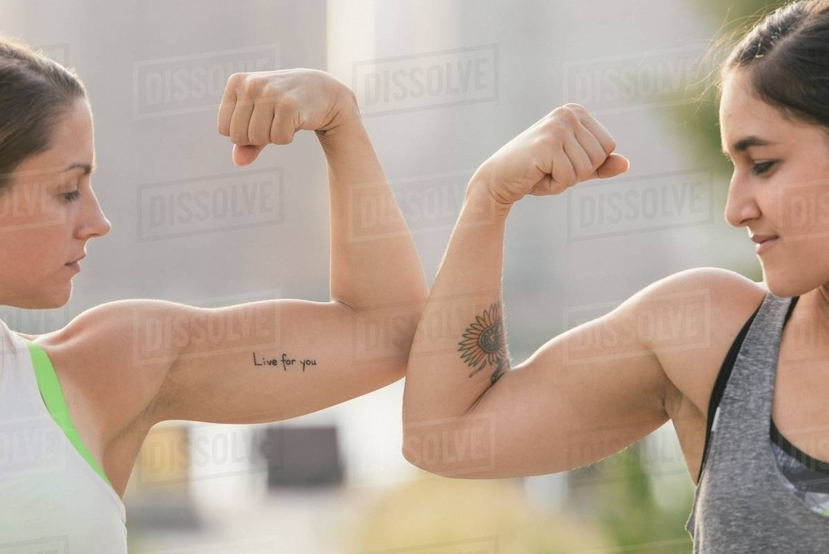 Two Friends Comparing Bicep Muscles Stock Photo Dissolve