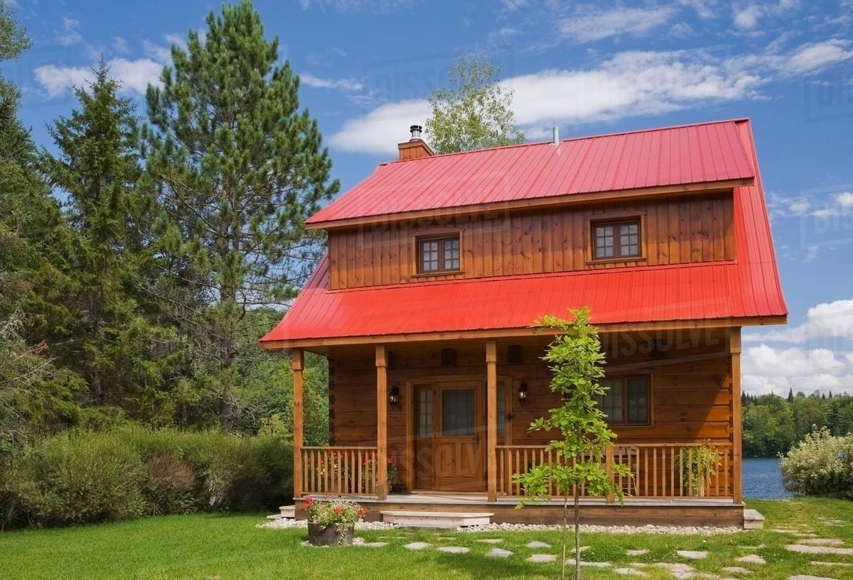 Small cottage style log home facade with red sheet metal roof and brown  trim in summer - Stock Photo - Dissolve