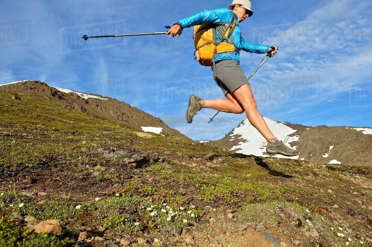 Female mountain climber jumping downhill, Chugach State Park, Anchorage, Alaska, USA Royalty-free stock photo