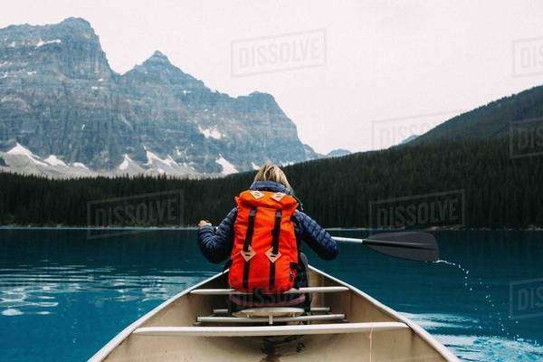 Rear view of mid adult woman paddling canoe, Moraine lake, Banff National Park, Alberta Canada Royalty-free stock photo
