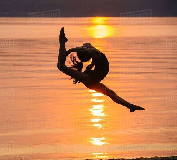 Side view of girl in silhouette by ocean at sunset in mid air, legs apart throwing head back Royalty-free stock photo