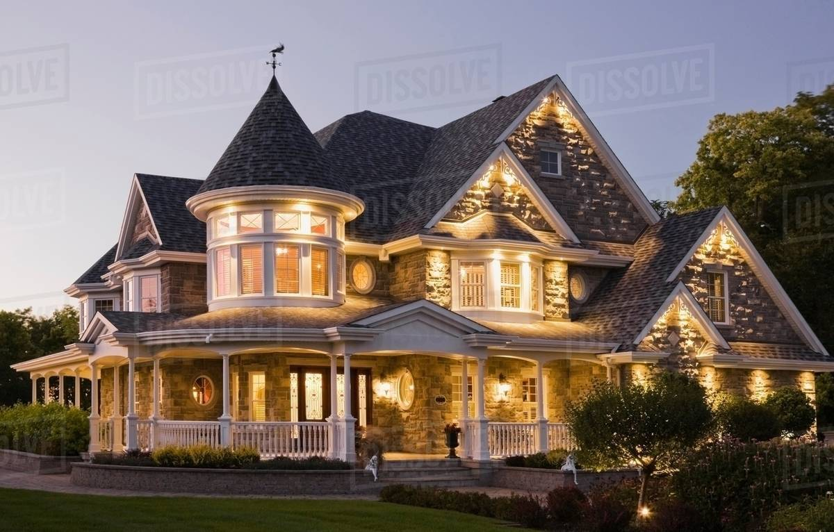 Elegant Grey Stone House With White Trim And Blue Roof At Dusk In Summer Quebec Canada