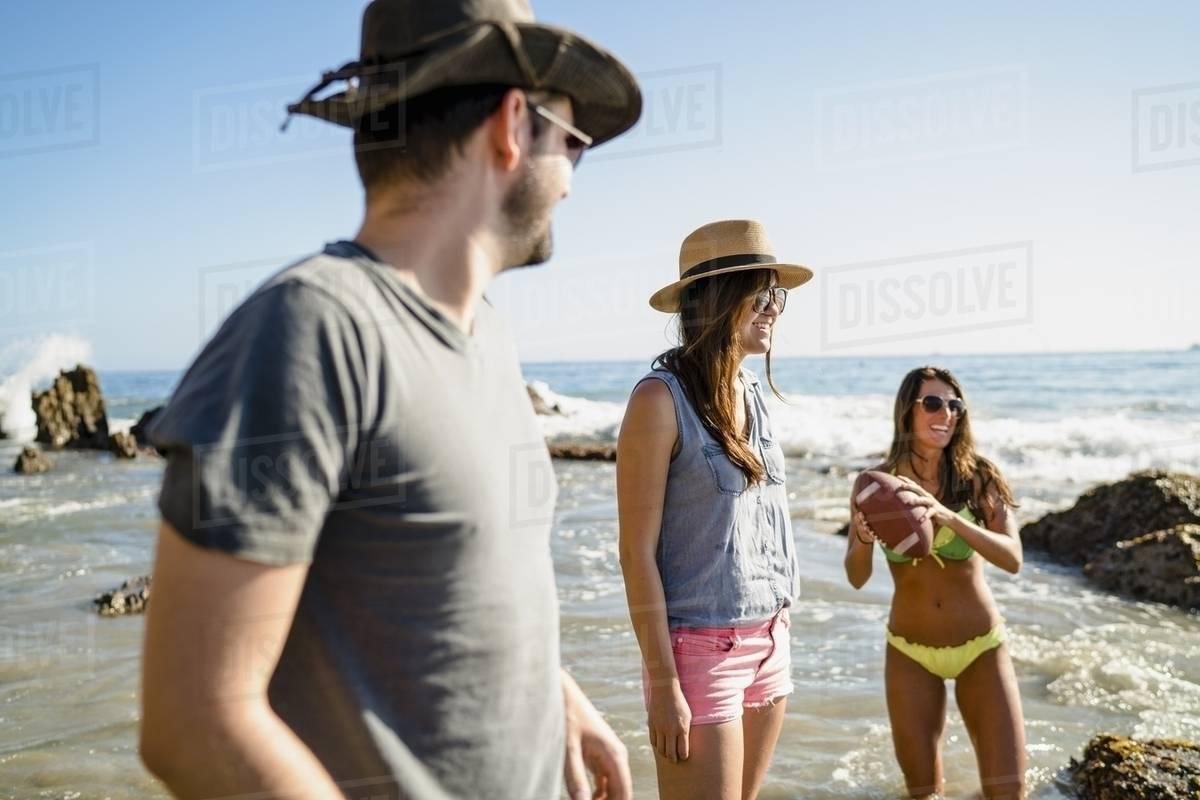 Three Friends Playing American Football In Sea At Newport Beach California Usa