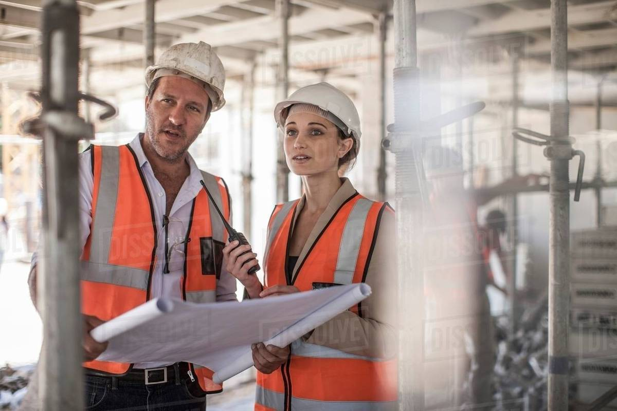 Female and male builders with blueprint on construction site stock female and male builders with blueprint on construction site malvernweather Image collections