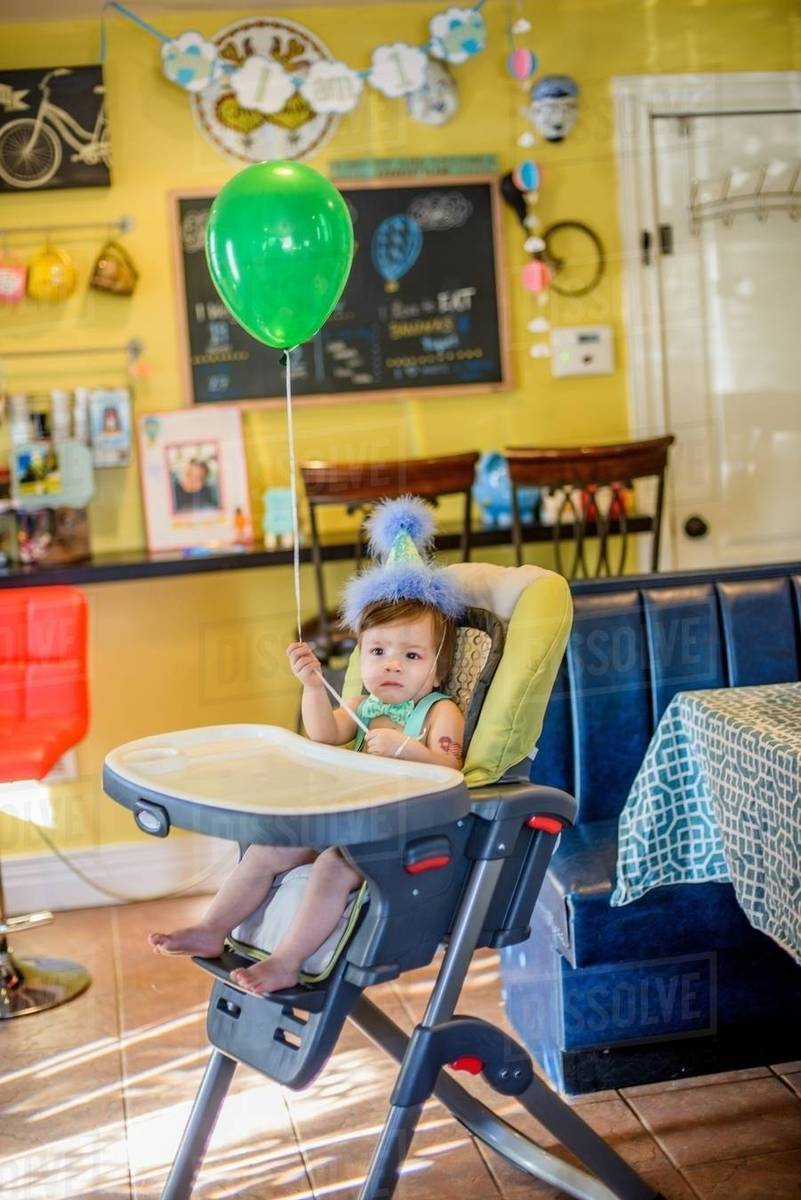 Portrait Of Baby Boy Wearing Birthday Party Hat Sitting In High Chair
