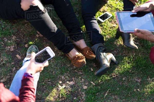 Group of female friends relaxing in park, using digital tablet and smartphone, low section Royalty-free stock photo