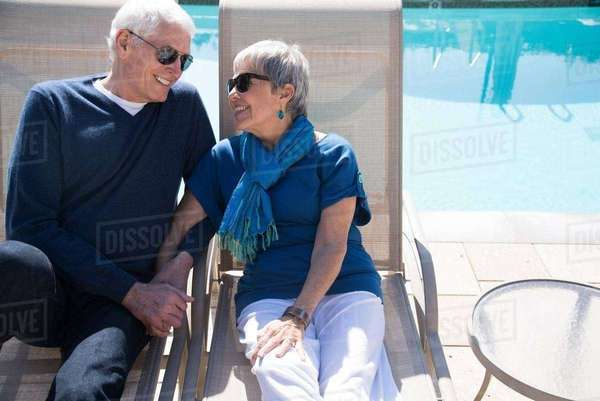 Senior couple relaxing on sun loungers beside pool Royalty-free stock photo