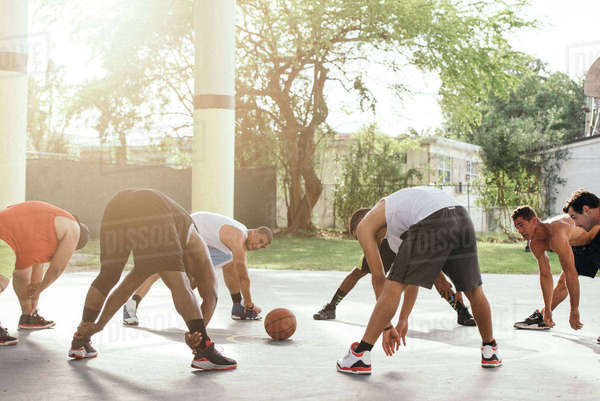 Friends on basketball court in a circle bending forwards warming up Royalty-free stock photo