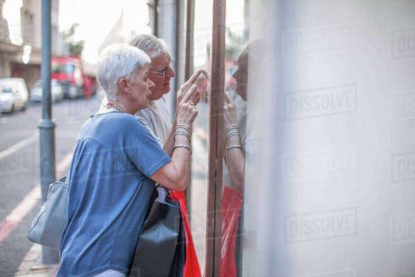 Senior couple pointing at city shop window Royalty-free stock photo