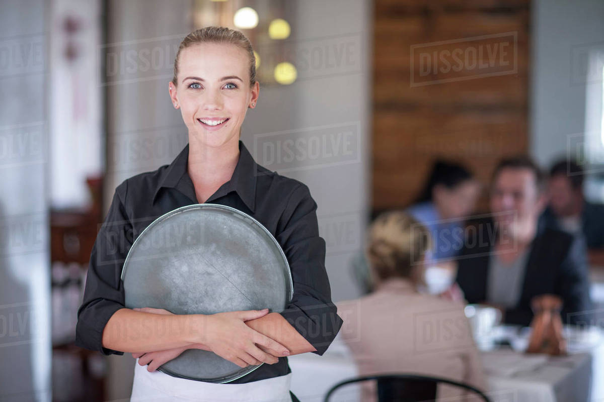 Waitress with serving tray in busy restaurant stock photo