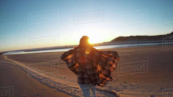 Rear view of woman wearing blowing shawl watching sunset from Cannon Beach, Oregon, USA Royalty-free stock photo