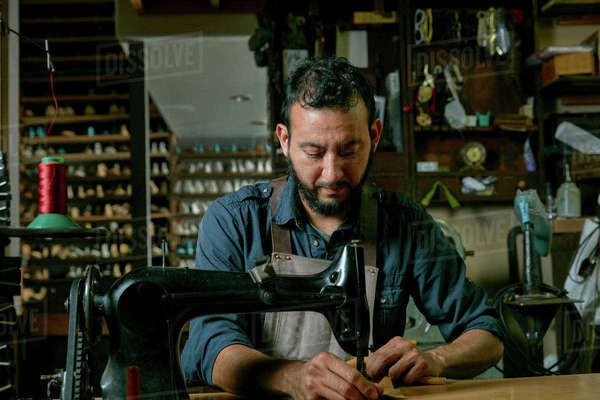 Male cobbler working at sewing machine in traditional shoe workshop Royalty-free stock photo