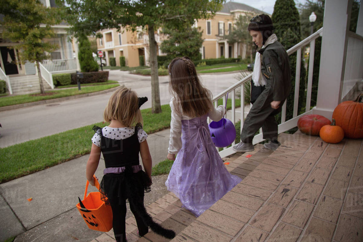 Boy and sisters trick or treating moving down porch stairway Royalty-free stock photo