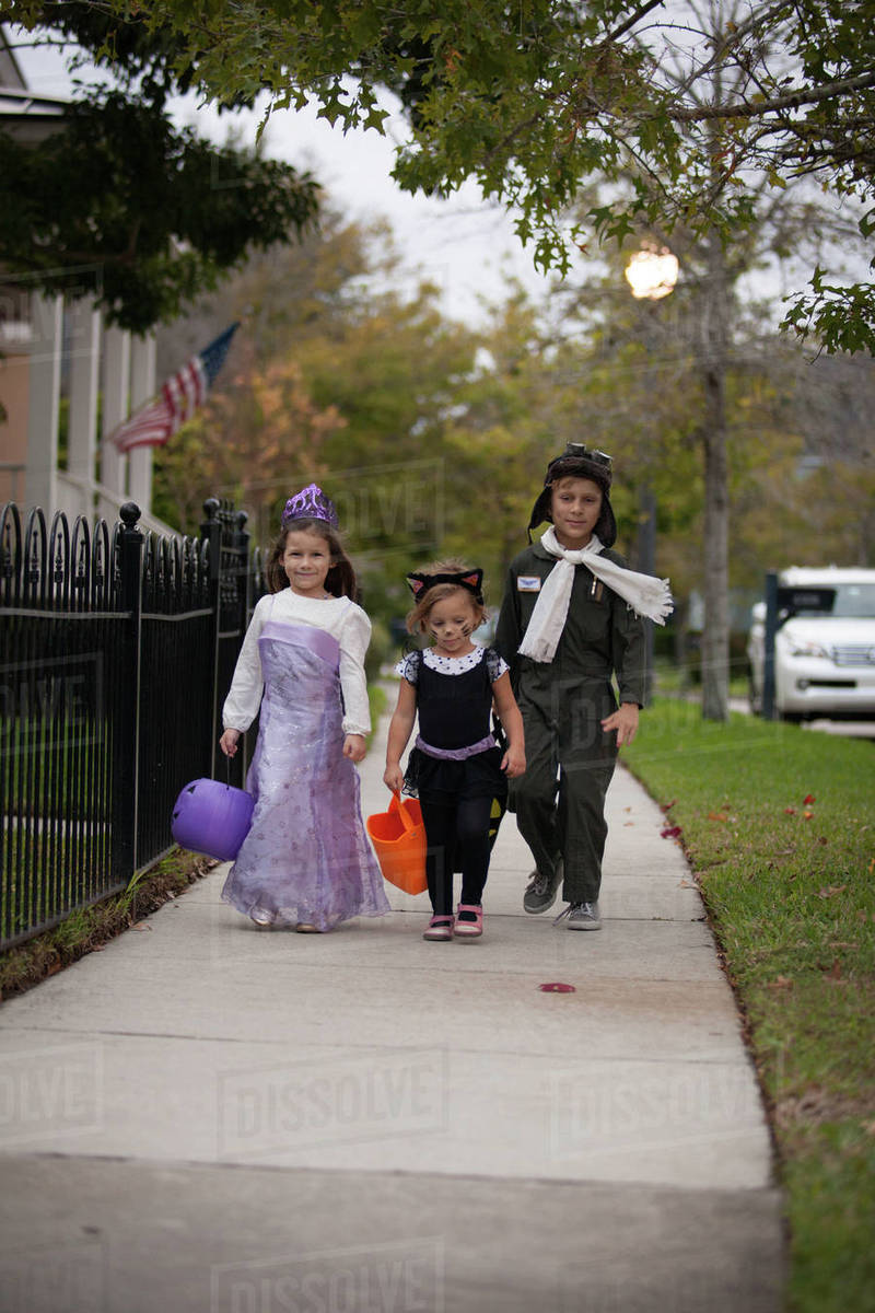 Boy and sisters walking along sidewalk trick or treating Royalty-free stock photo