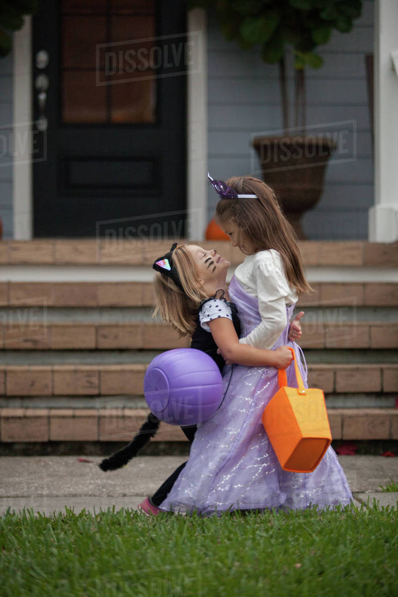 Two sisters trick or treating in cat and fairy costumes hugging at porch stairway Royalty-free stock photo