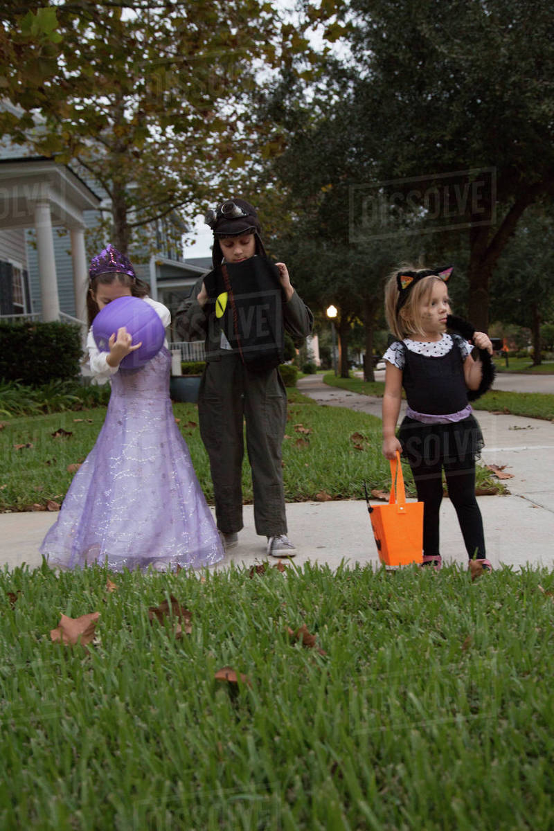 Boy and sisters trick or treating looking in bags on sidewalk Royalty-free stock photo
