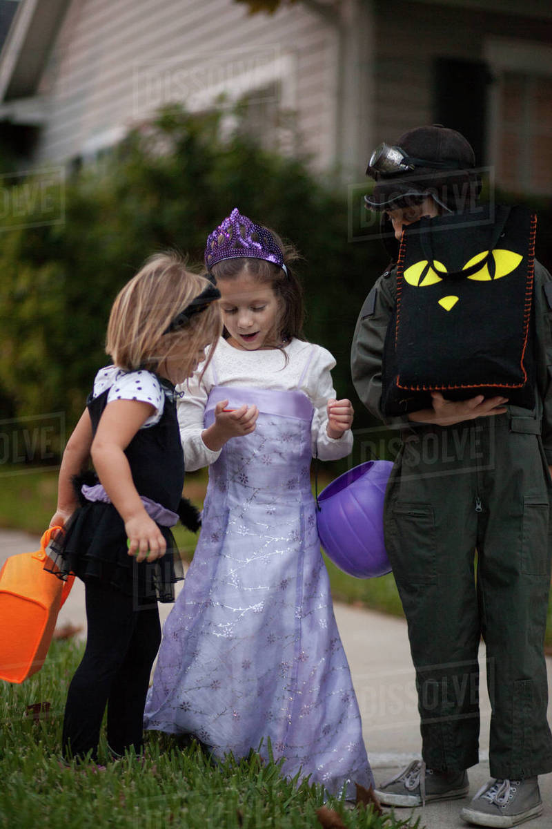 Boy and sisters trick or treating looking at treats on sidewalk Royalty-free stock photo