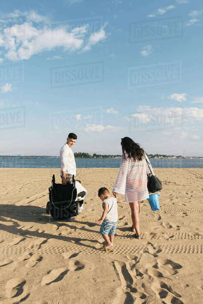 Rear view of parents holding hands with toddler son on beach at Pelham Bay Park, Bronx, New York, USA Royalty-free stock photo