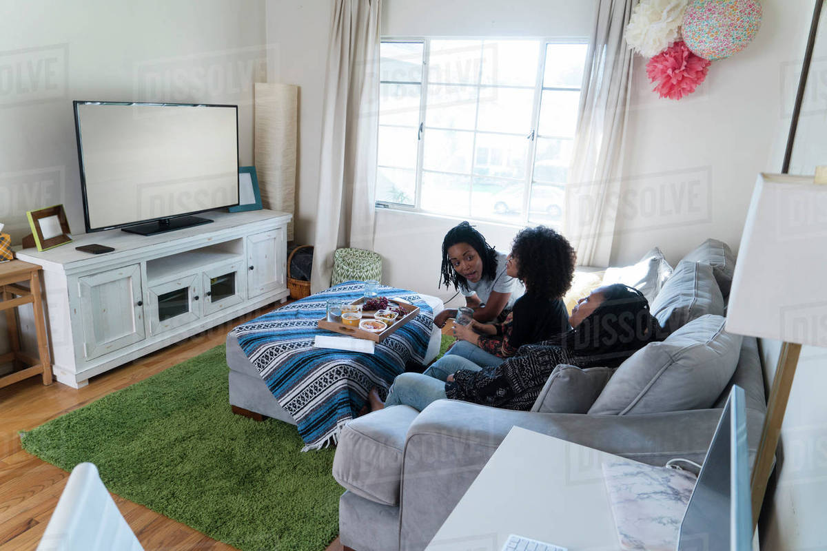 three female friends relaxing at home watching tv stock. Black Bedroom Furniture Sets. Home Design Ideas