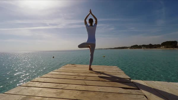 Medium point-of-view shot of woman practicing yoga on wooden pier Royalty-free stock video