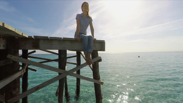 Medium point-of-view shot of woman sitting on wooden pier Royalty-free stock video