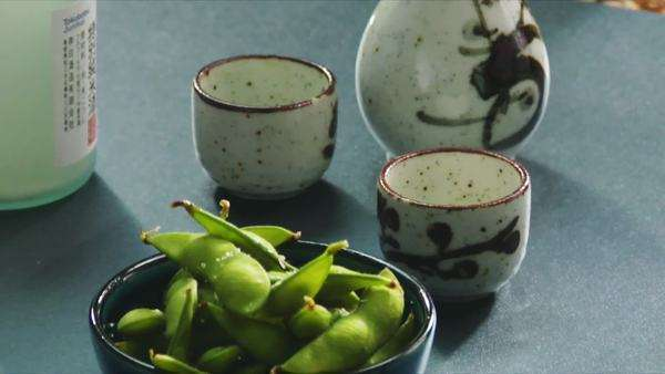 Sprinkling soya beans with salt, sake bottle and cups Royalty-free stock video