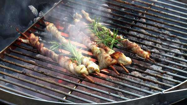 Belly pork wrapped around skewers with rosemary on barbecue Rights-managed stock video