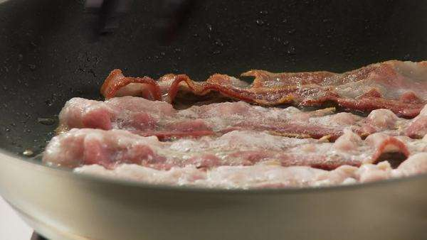 Rashers of bacon being fried and turned in a pan Royalty-free stock video
