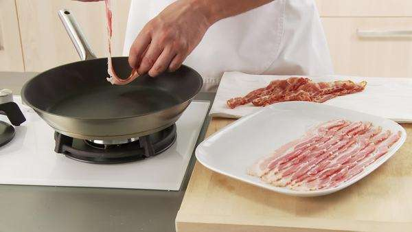 Rashers of bacon being placed in a pan Royalty-free stock video
