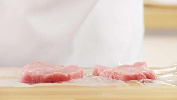 Veal escalopes being tenderised between layers of clingfilm Royalty-free stock video
